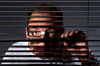Man peering through blinds