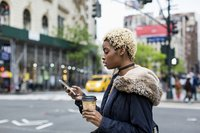 Woman drinking coffee and checking phone