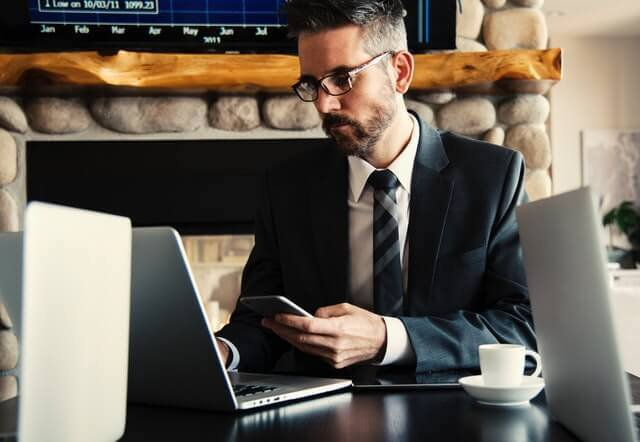 Man in suit using a laptop and phone